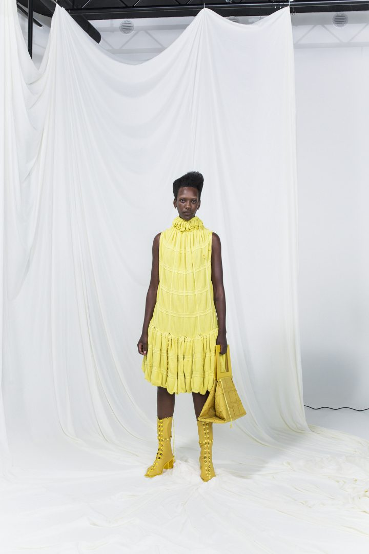 Model is wearing a yellow sleeveless modular mid-dress with matching yellow leather bag and heeled boots