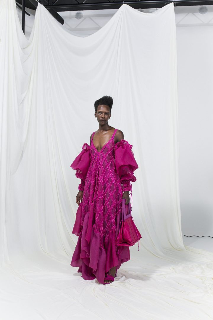 Model is wearing a flowy pink modular dress with detached sleeves. Accompanied by matching pink handbag