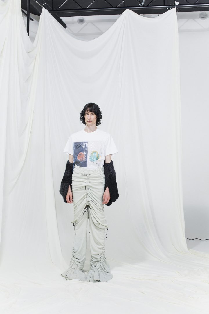 Model is wearing a printed and coated white t-shirt with black armcuffs. Over these are draped white trousers