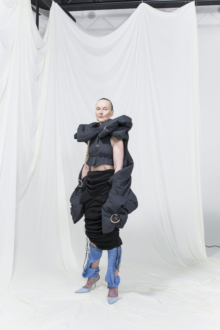 Model is wearing a black manipulated vest with massive sleevecuffs and golden embellishments, black slim skirt and blue heels