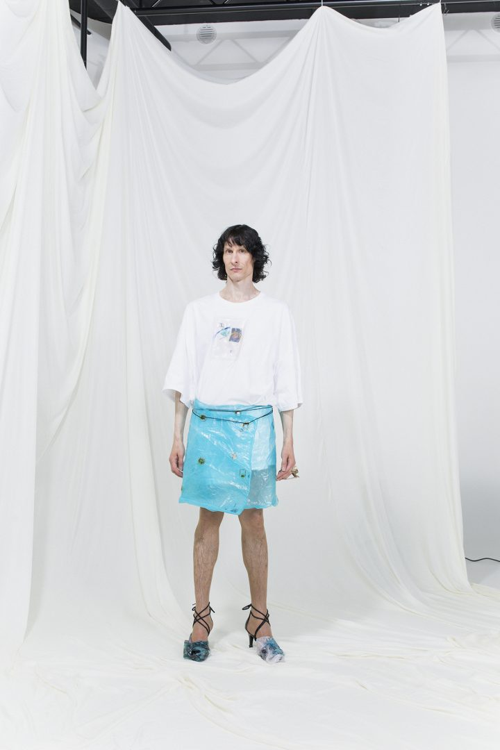 Model is wearing a white coated t-shirt and light blue wrap skirt with experimental heels
