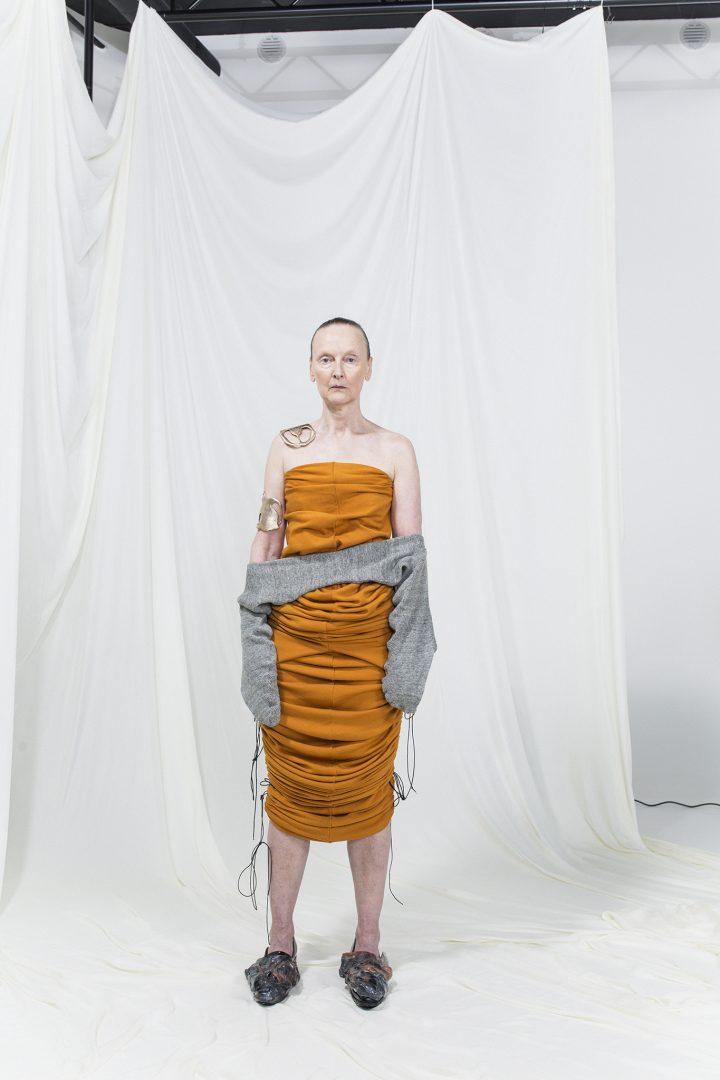 Model is wearing a sleeveless slim draped orange midi-dress with grey infinity-gloves