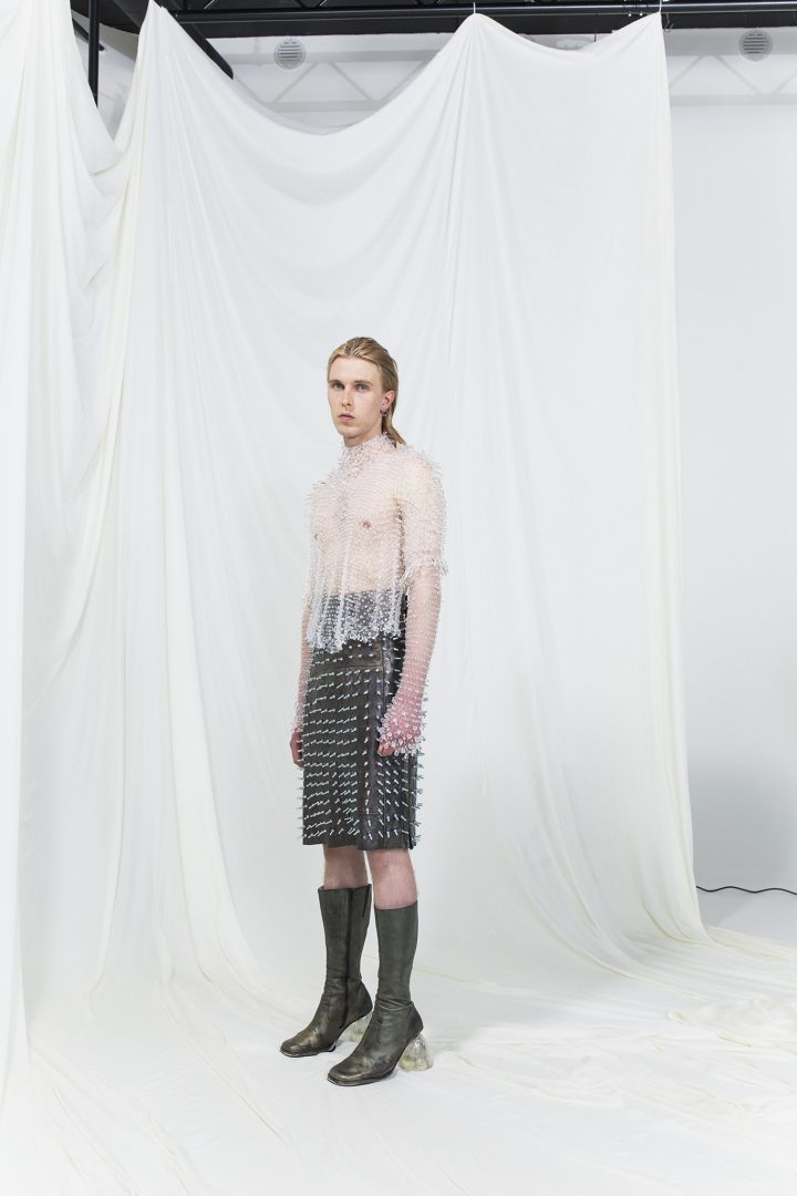 Model is wearing a studded leather skirt and sheer white top with crystals