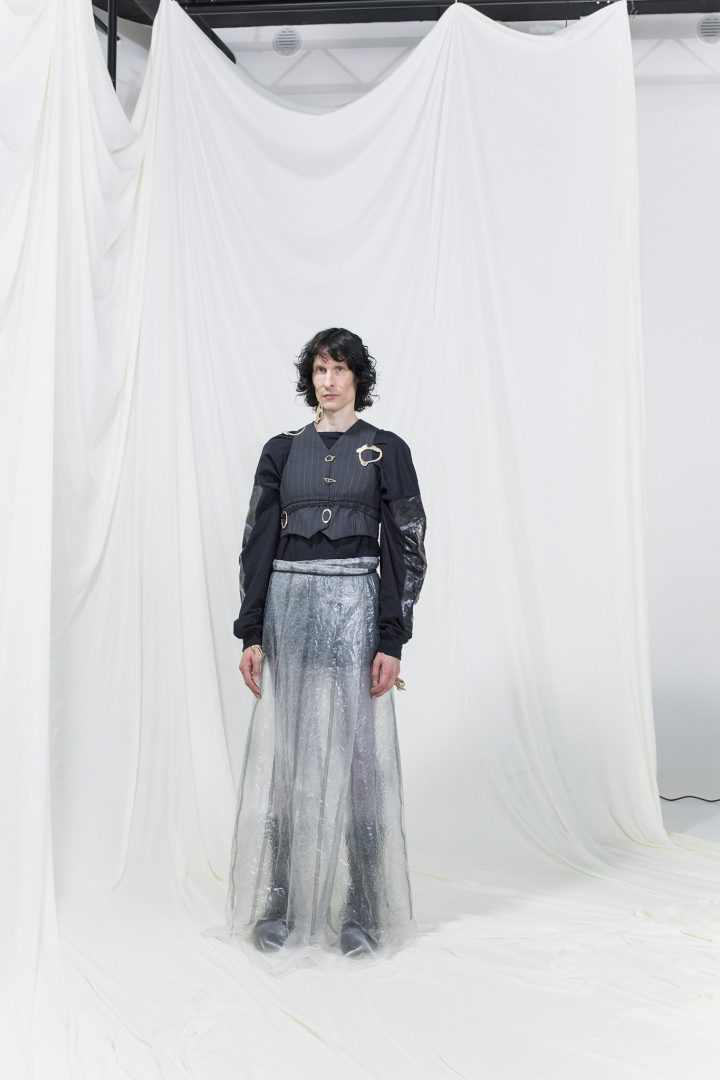 Model is wearing a black top with pinstripe vest, accompanied by sheer wrap skirt