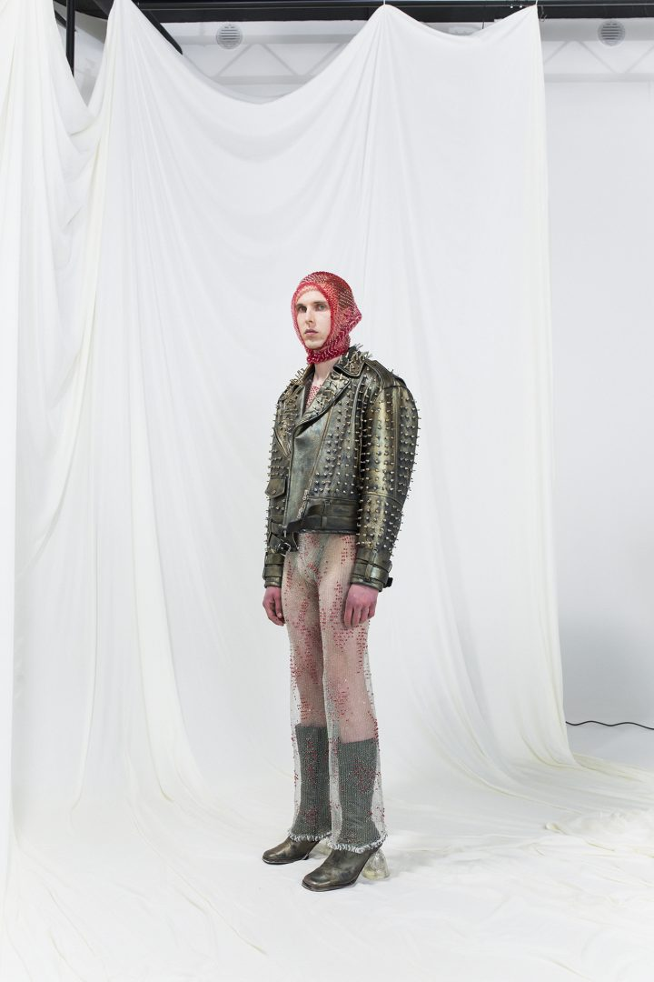 Model is wearing a long sheer dress with red chrystals and metallic olive green-golden leather jacket