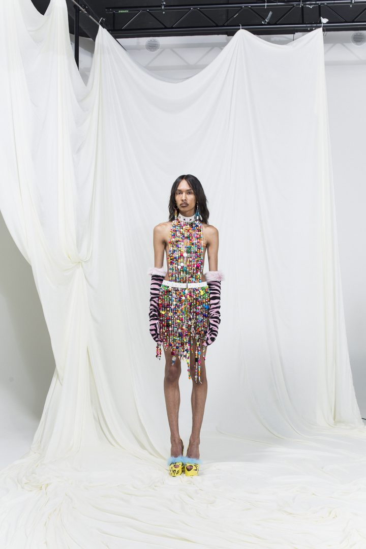 Model is wearing a multicoloured pearl-fringed top and skirt, pink zebra printed gloves and high-heels