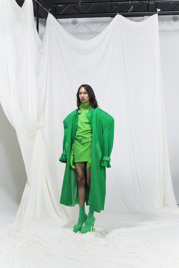 Model wearing a bright green trench coat with green dress, gloves and green high heels.