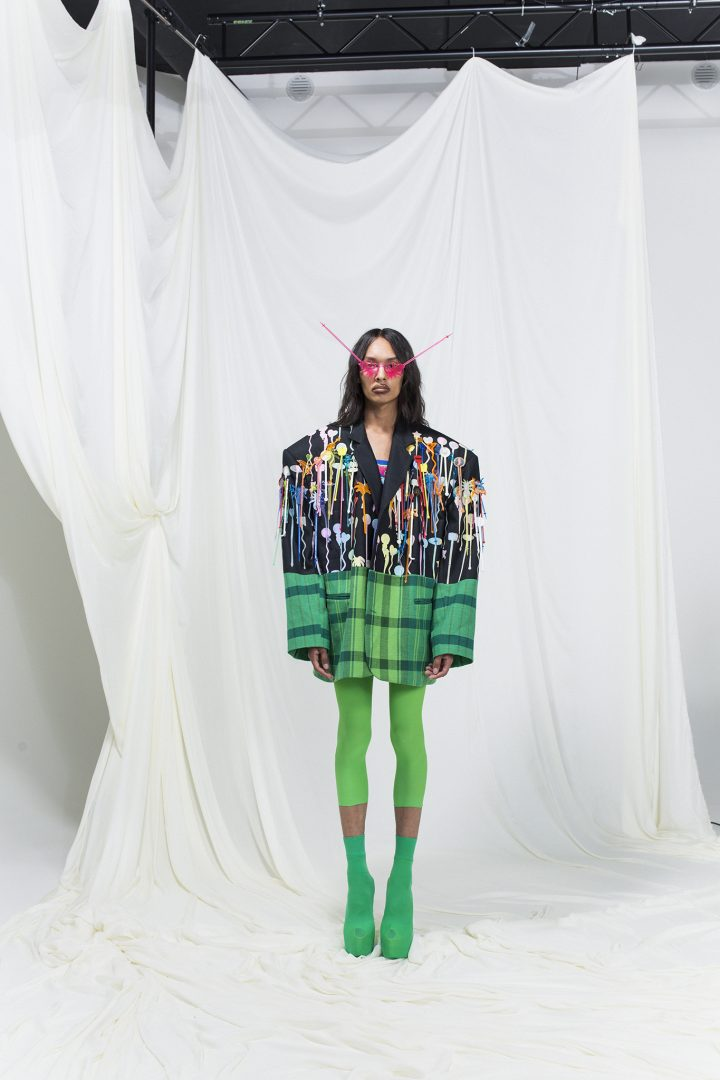 Model wearing an oversized blazer embroidered with cocktail sticks, green leggings and high heels, cocktail sticks as sunglasses.