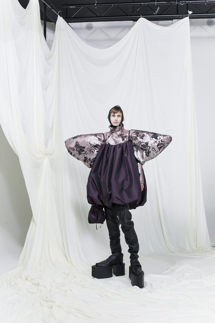 Model is wearing a purple balloon-shaped dress and printed shirt with exaggerated sleeves underneath. Headscarf and long black boots as accessories