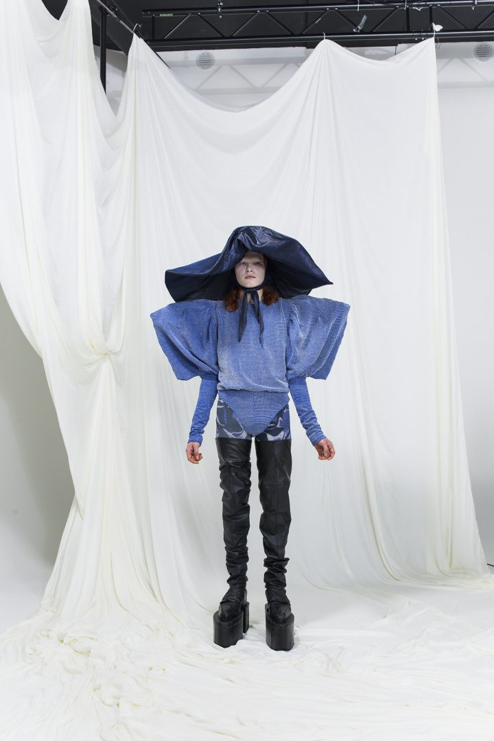 Model is wearing a blue bodysuit with exaggerated shoulders and sleeves. Wide-brim dark blue hat as an accessory