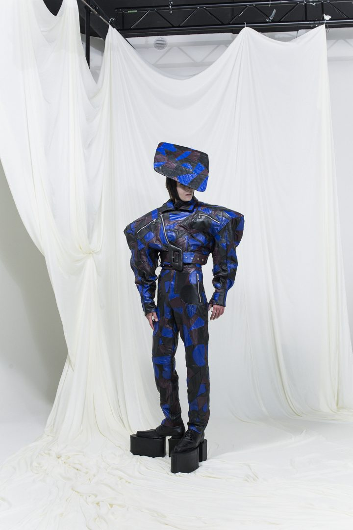Model is wearing a patchwork leather jacket with exaggerated shoulders, matching headpiece and slim trousers