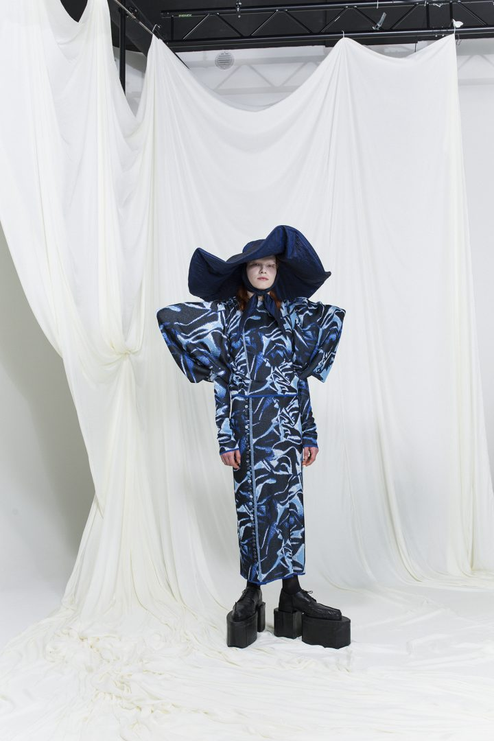 Model is wearing a knitted robe dress with distorted blue pattern and exaggerated shoulders and sleeves. Wide-brim dark blue hat as an accessory