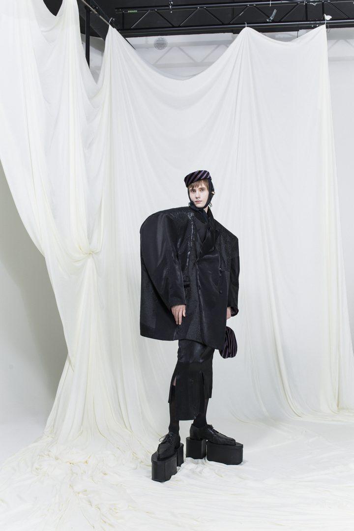 Model is wearing an oversized black blazer, slim black skirt and striped hat