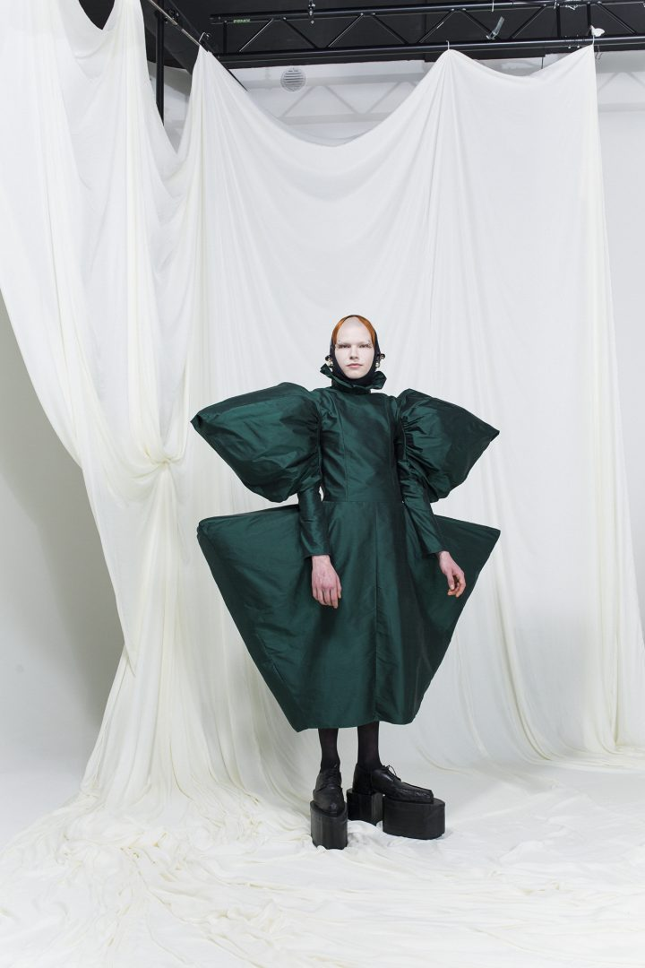 Model is wearing a emerald green dress with puffy angular shoulders and wide hips