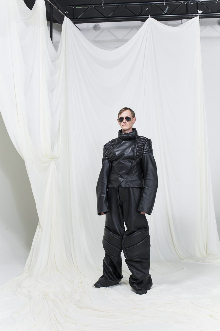 Model is wearing oversized padded leather jacket with matching pants