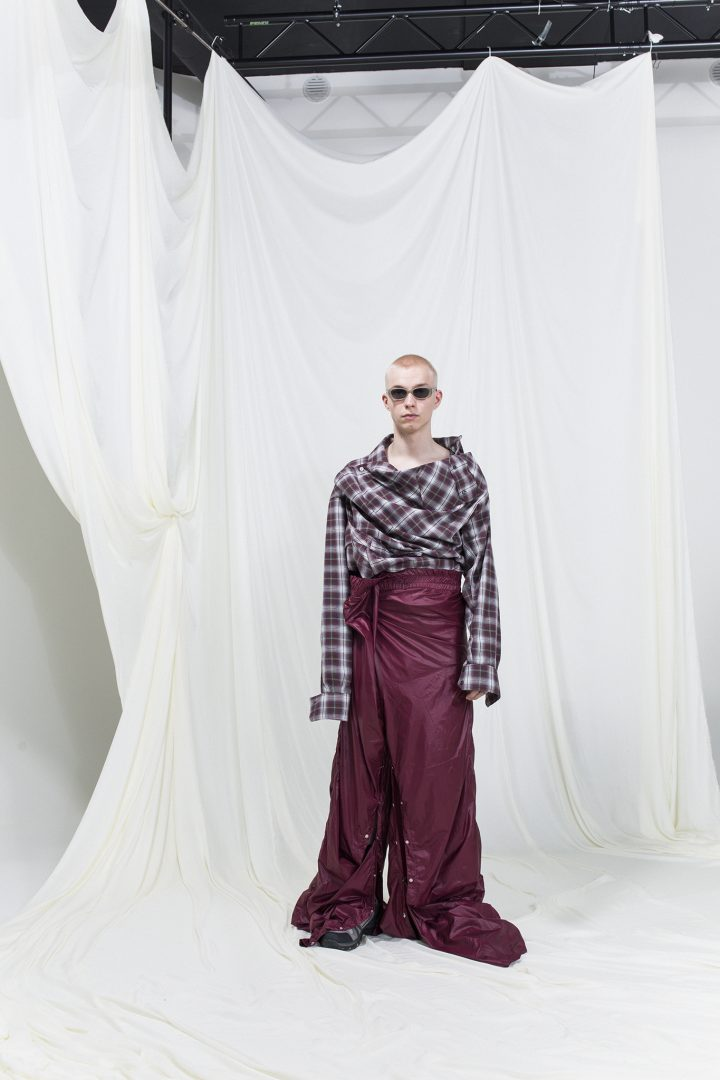 Model is wearing an oversized brown checked shirt and burgundy tracksuit pants