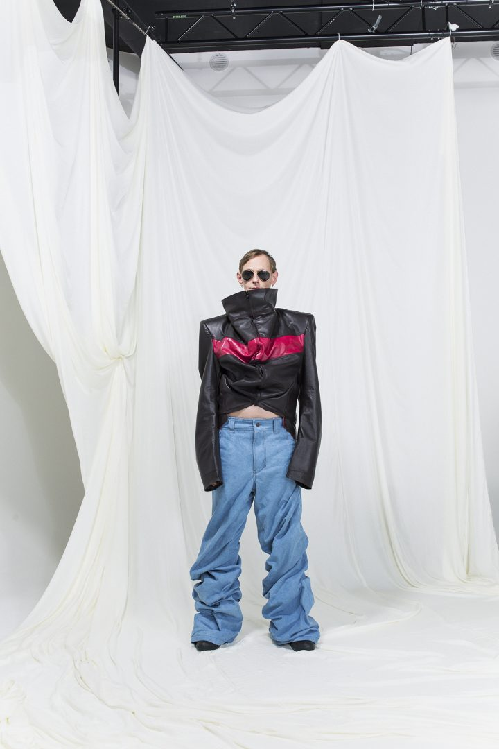 Model is wearing a oversized leather jacket with red stripe and oversized jeans