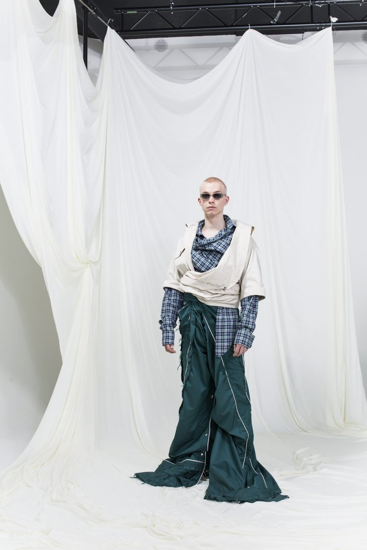 Model is wearing oversized shirt and tracksuit pants in green, sunglasses