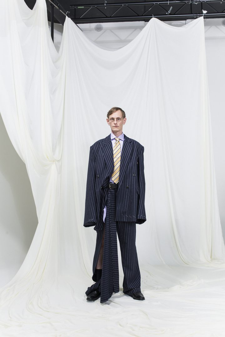 Model is wearing a pinstripe oversized suit with slit on right leg