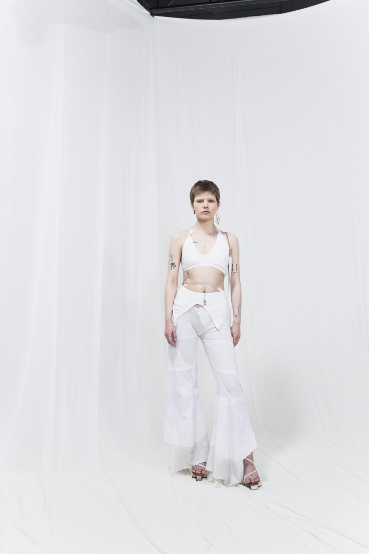 Model is wearing a white top and white bell-bottomed draped trousers