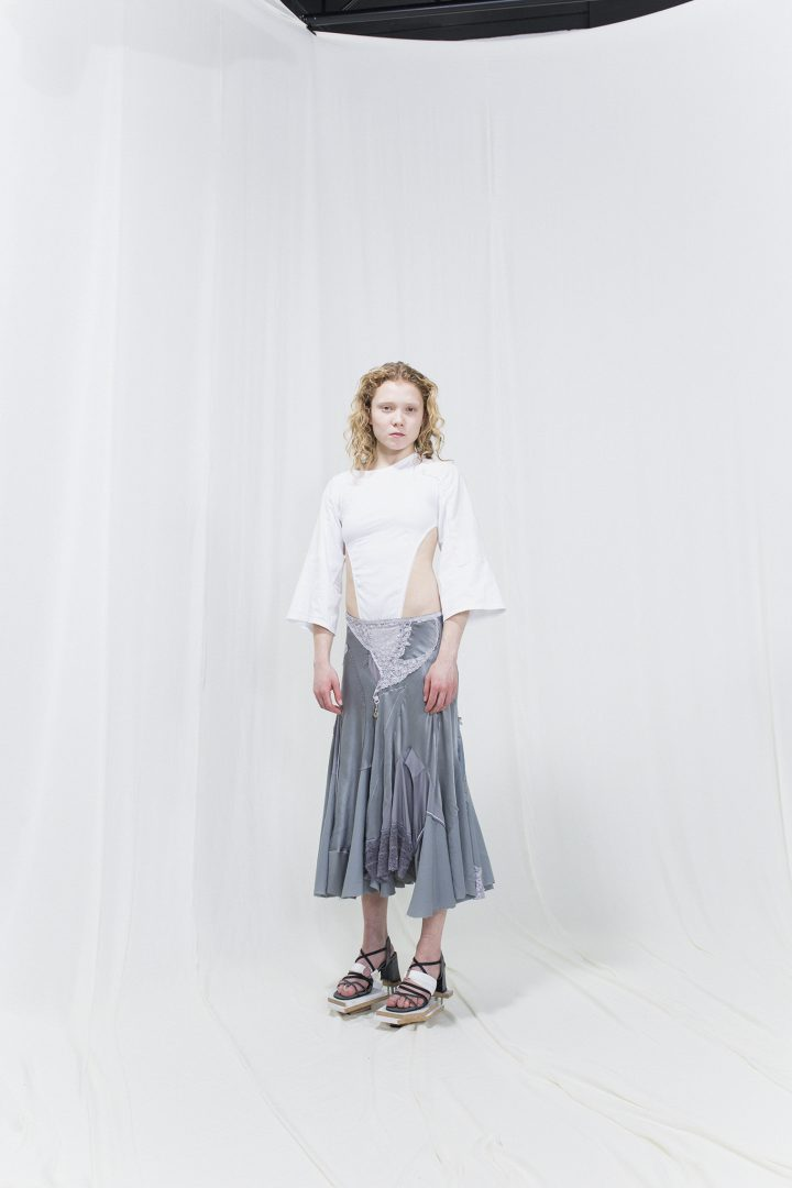 Model is wearing a white 3/4 sleeved top with cuts in the front and bias-cut silver skirt