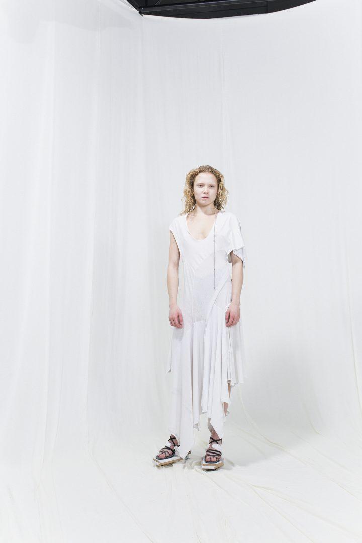 Model is wearing a white asymmetric dress