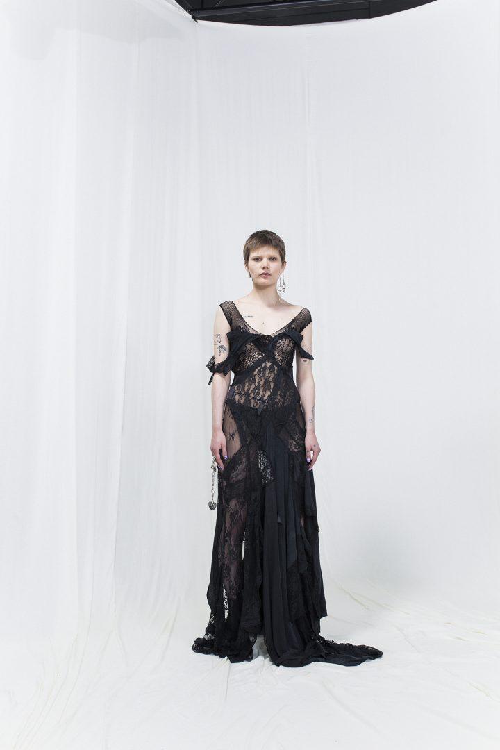 Model is wearing a black asymmetric lace gown
