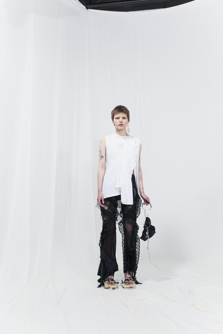 Model is wearing a white draped top with draped sheer trousers. black bag as accessory
