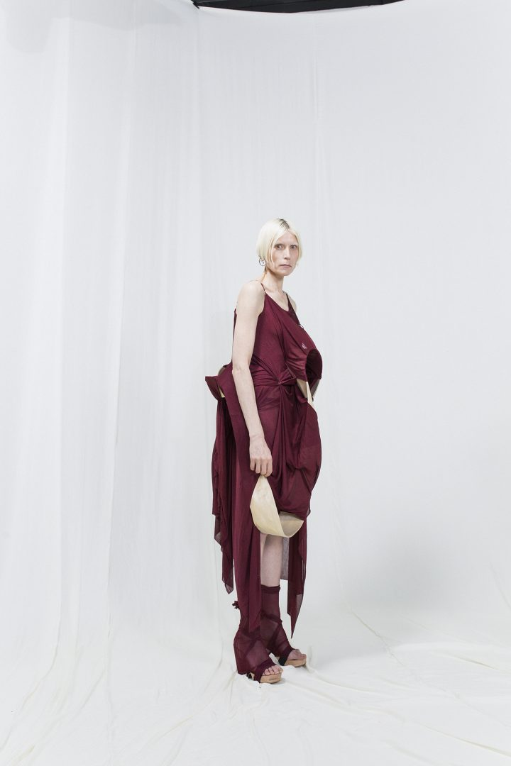 Model is wearing a burgundy dress wit bended birch piece attached