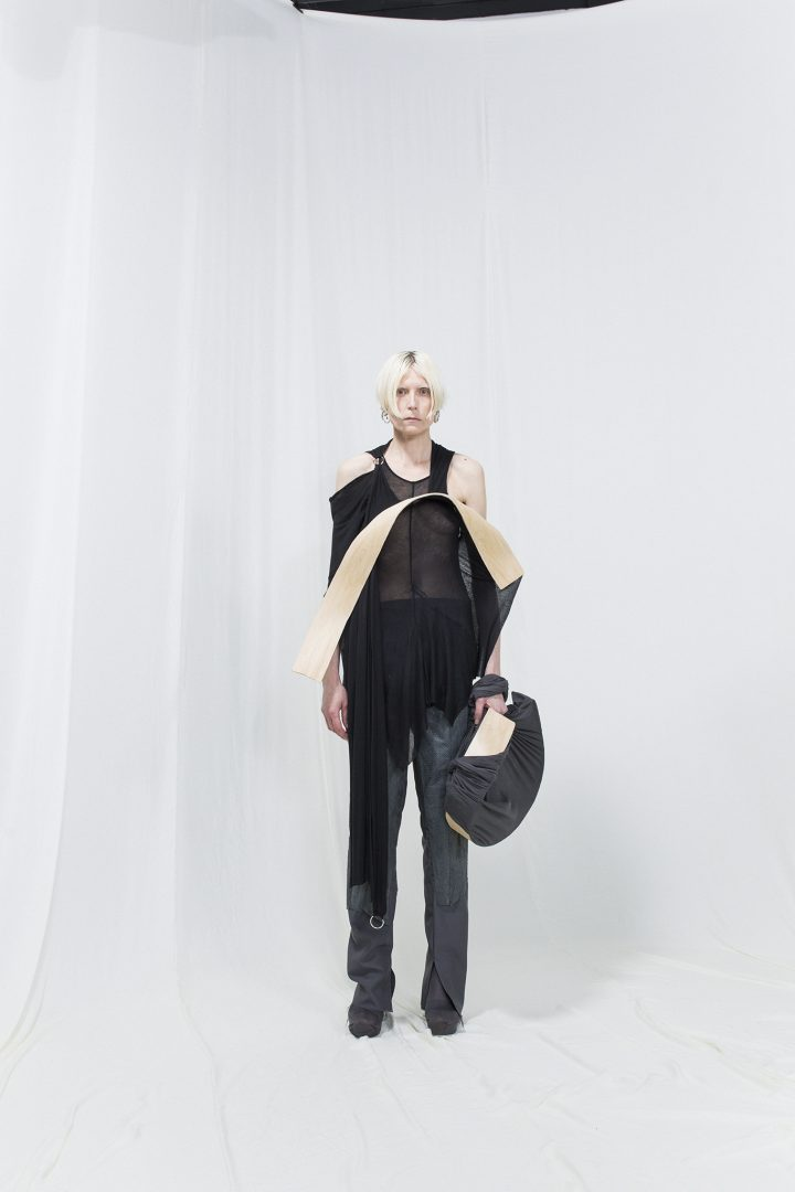 Model is wearing an asymmetrical black top with bended birch piece attached, matching bag and grey trousers underneath