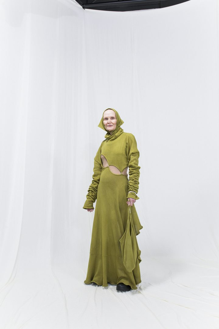 Model is wearing a long knitted green dress with matching bag and headscarf