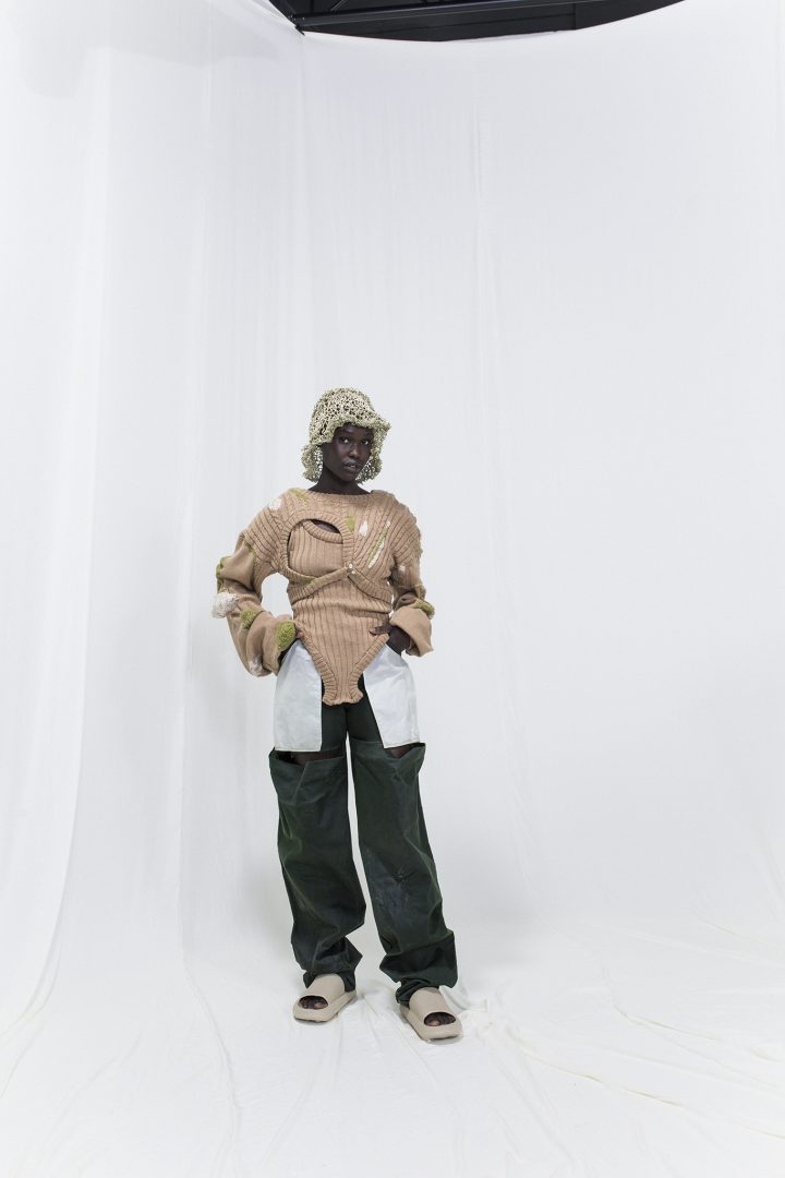 Model is wearing a mended knitted sweater with matching knitted bodysuit. Oversized linseed-oil coated green trousers with white pockets underneath