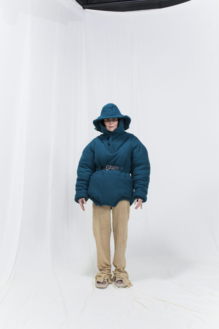 Model is wearing a petroleum blue felted anorak with hat-hood and knitted linen trousers