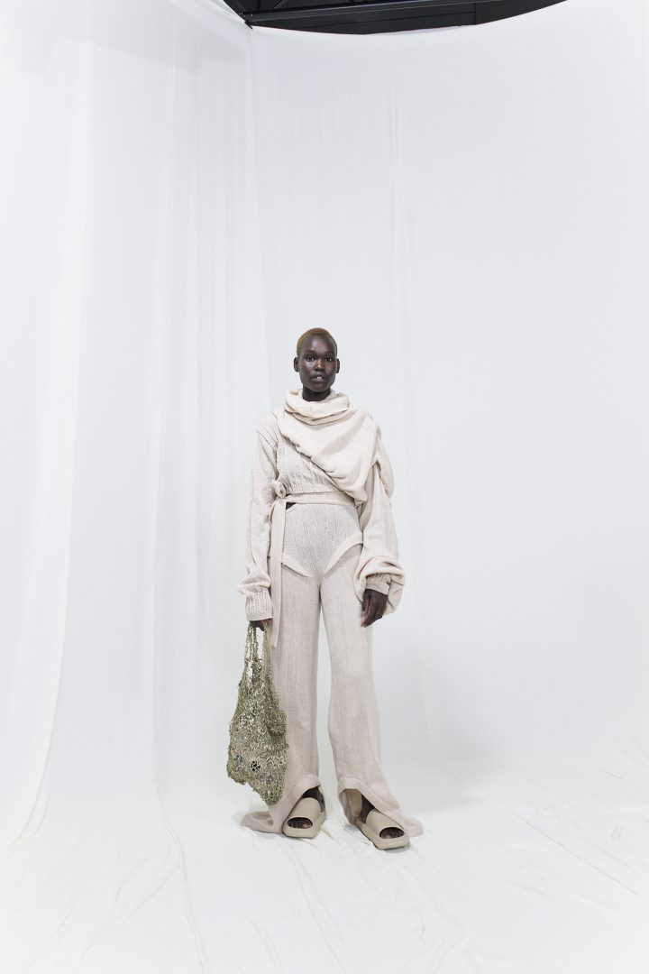 Model is wearing a beige draped and knitted sweater with matching knitted trousers. Slippers and knitted seaweed bag as accessories