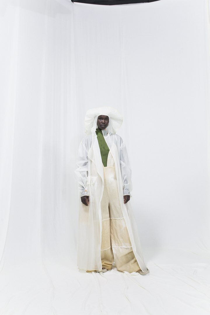 Model is wearing a long linseed-oil coated jacket with fisherman hat and oversized overalls. Green knitted jumpsuit underneath