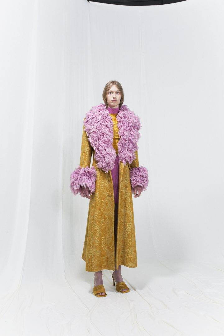 Model is wearing a long ochre coat with flamboyant furry collar and sleeve cuff details
