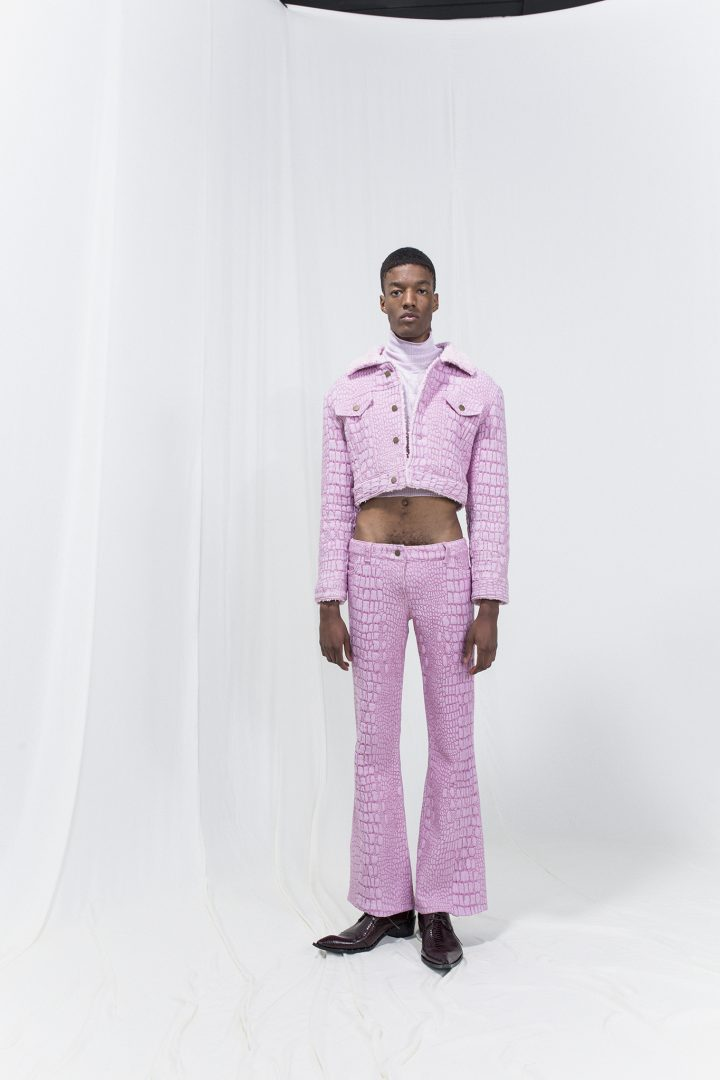 Model is wearing a pale pink cropped turtleneck, short crocodile-imitation jacquard-woven jacket with matching trousers