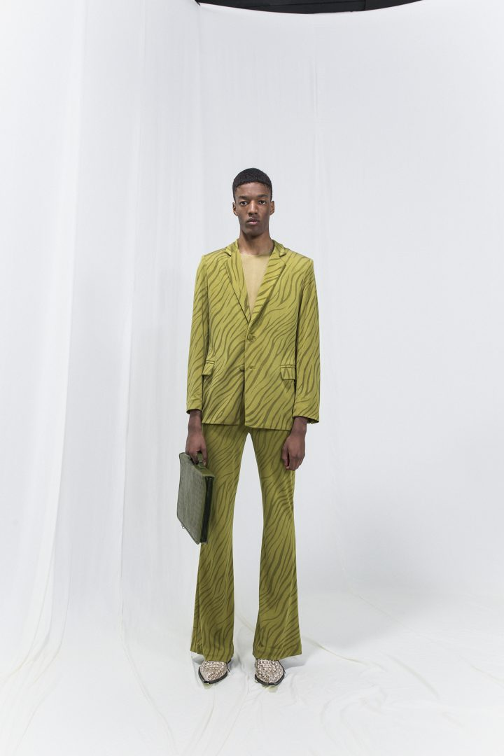Model wearing an olive green zebra printed jersey blazer, matching bell-bottomed trousers and green suitcase