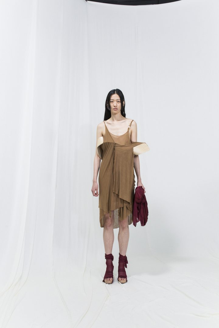 Model is wearing a brown slip-on dress with bended birch piece attached, burgundy bag