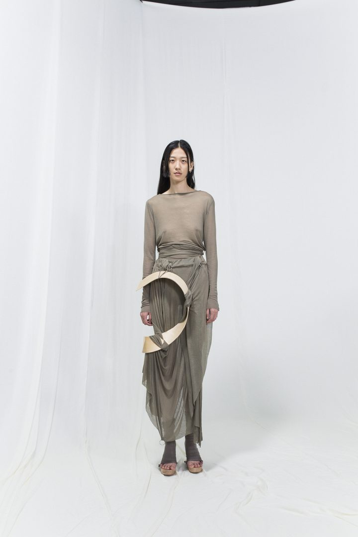 Model wearing a grey jersey dress with bended birch piece attached