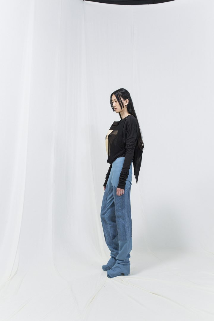 Model is wearing a black jersey sweater with bended birch piece attached, with blue jeans.
