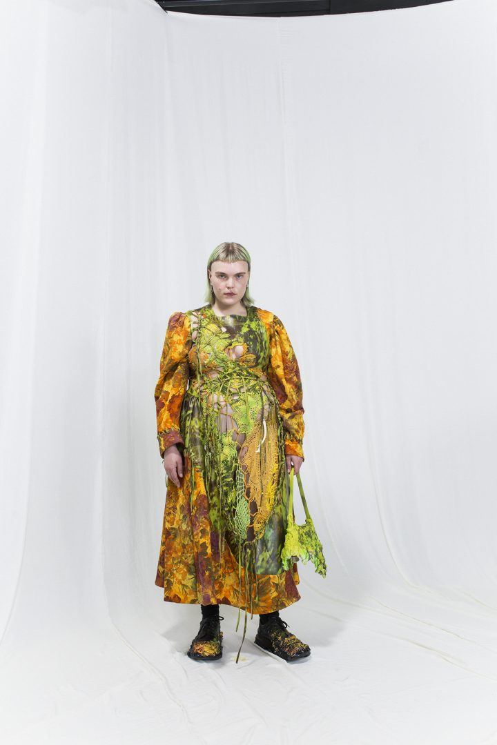Model waring a multicoloured dress with cutouts, green melting bag.