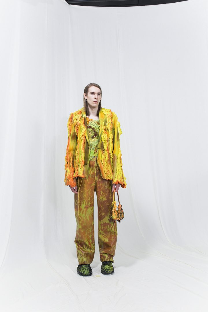 Model is earring a multicoloured jacket with crochet top underneath, brown & green marble printed trousers, orange melting bag