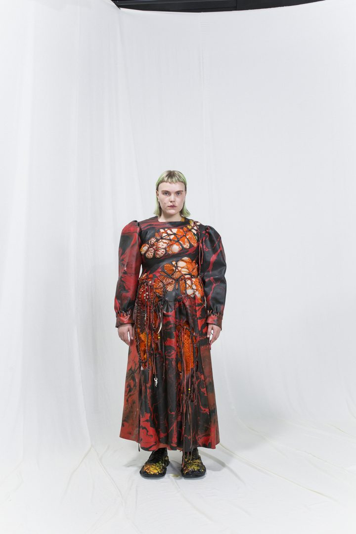 Model is wearing a black & red marbled dress with cut-outs, orange crochet dress underneath.