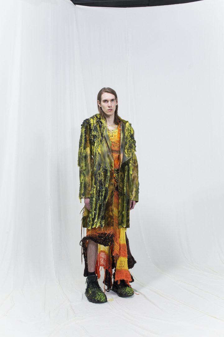 Model is wearing a black & green leather coat, orange & crochet dress