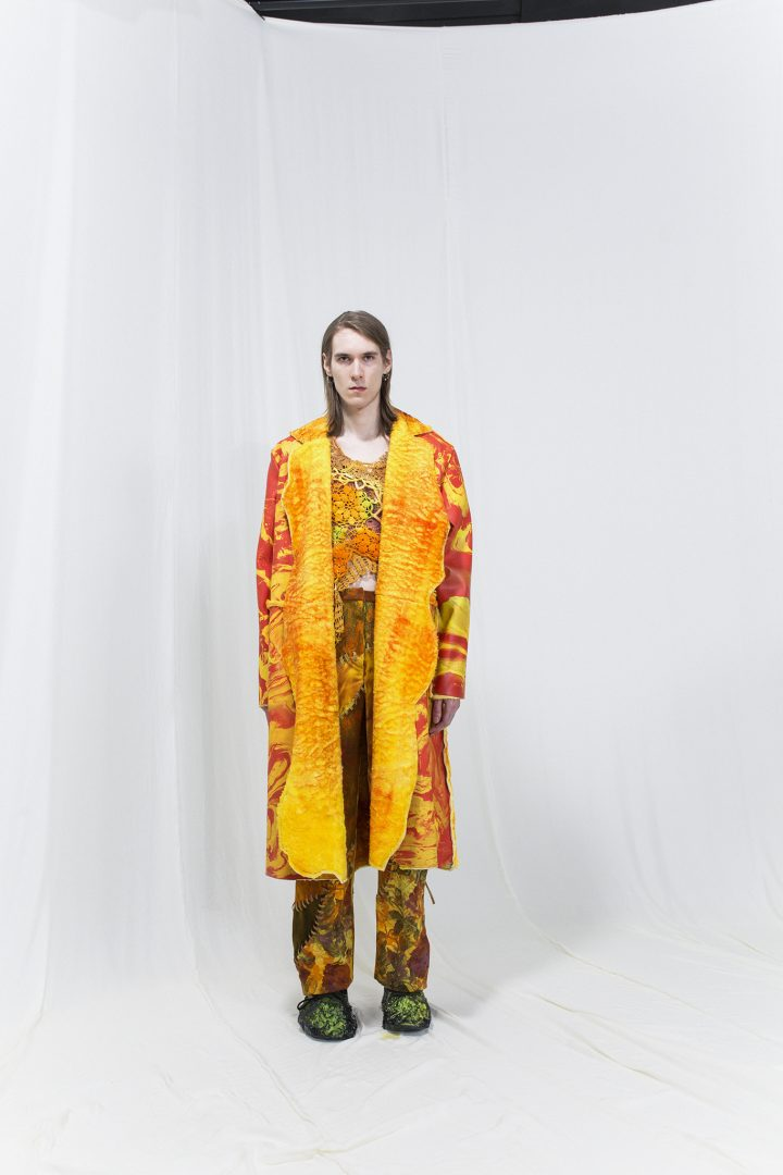 Model wearing a red & yellow marbled shearling coat with crochet top underneath, matching trousers