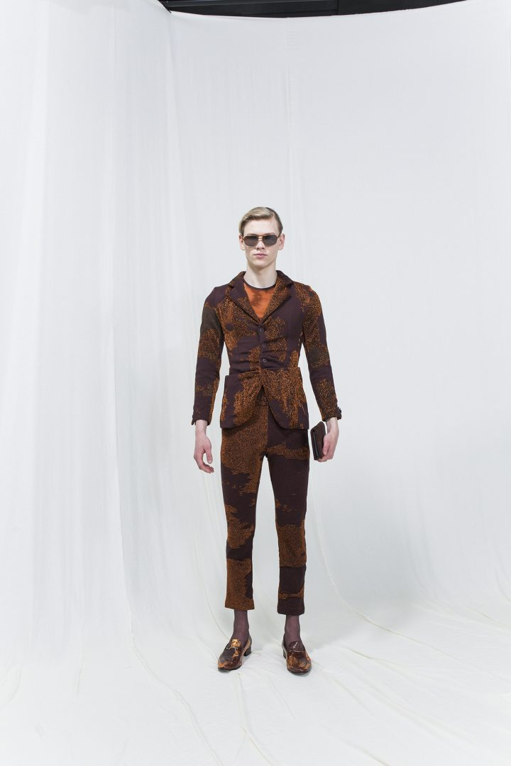 Model is wearing a printed brown blazer with gatherings and matching cropped trousers. Sunglasses and brown wallet as accessories