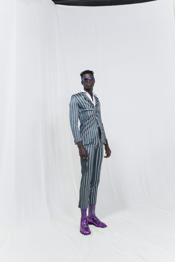 Model is wearing a green striped suit with gatherings and matching cropped trousers. Lilac socks, shoes and sunglasses as accessories
