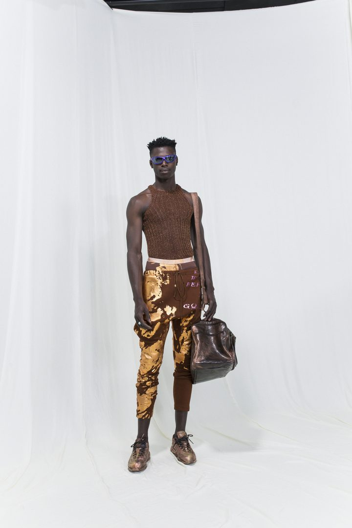 Model is wearing a brown ribbed top with brown-golden cropped trousers and oversized travel bag