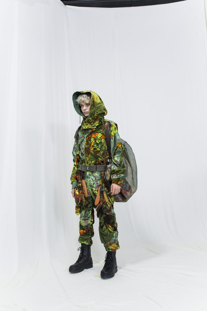 Model is wearing a multicoloured floral jacket with matching pants and a hood, see through rucksack